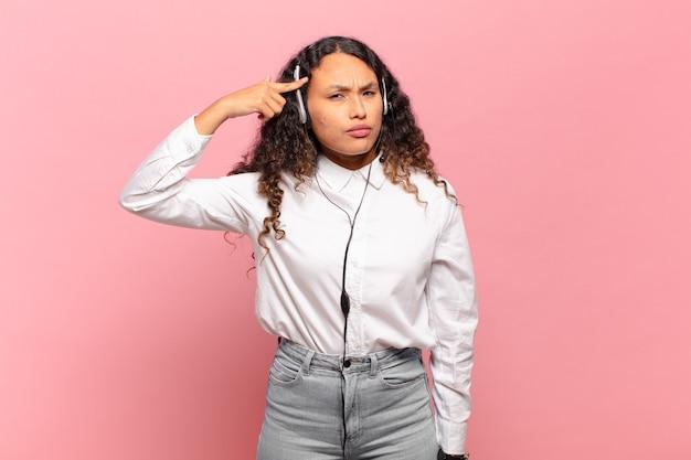 Jeune femme hispanique se sentant confuse et perplexe, montrant que vous êtes folle, folle ou folle. concept de télévendeur