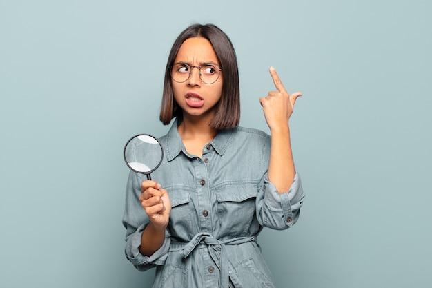 Jeune femme hispanique se sentant confuse et perplexe, montrant que vous êtes folle, folle ou folle