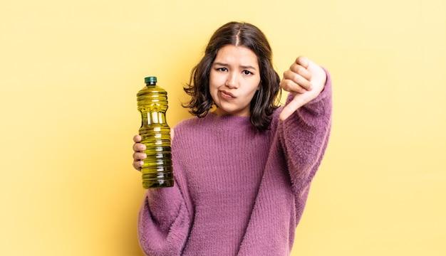 Jeune femme hispanique se sentant croisée, montrant les pouces vers le bas. concept d'huile d'olive