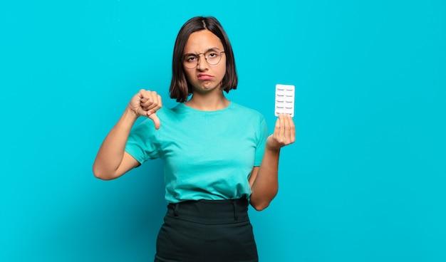 Jeune femme hispanique se sentant cross, en colère, ennuyé, déçu ou mécontent, montrant les pouces vers le bas avec un regard sérieux