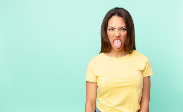 Jeune femme hispanique se sentant dégoûtée et irritée et tirer la langue