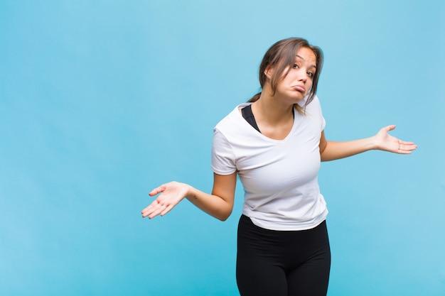 Jeune femme hispanique se sentant désemparée et confuse, n'ayant aucune idée, absolument perplexe avec un regard stupide ou stupide