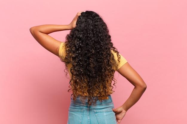 Jeune femme hispanique se sentant désemparée et confuse, pensant à une solution, avec la main sur la hanche et l'autre sur la tête, vue arrière