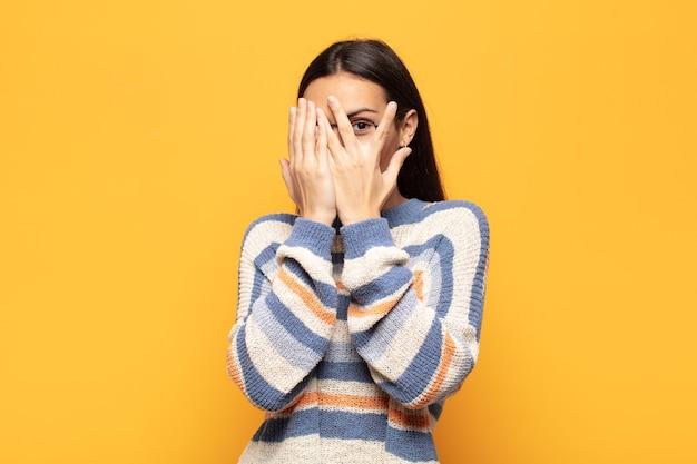 Jeune femme hispanique se sentant effrayée ou gênée, furtivement ou espionnant avec les yeux à moitié couverts de mains
