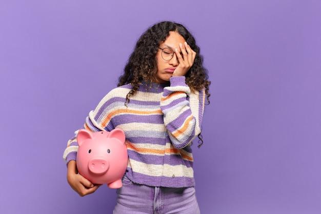 Jeune femme hispanique se sentant ennuyée, frustrée et somnolente après une tâche fatigante, ennuyeuse et ennuyeuse, tenant le visage avec la main. concept de tirelire
