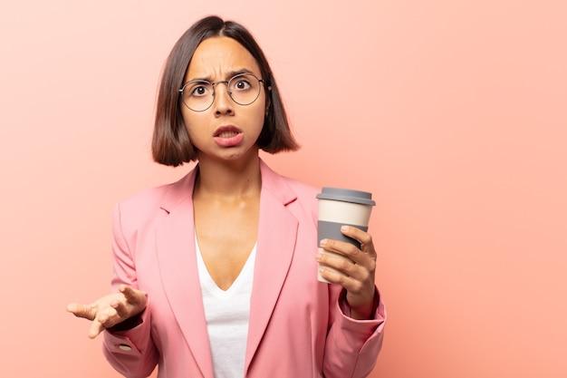 Jeune femme hispanique se sentant extrêmement choquée et surprise, anxieuse et paniquée, avec un regard stressé et horrifié