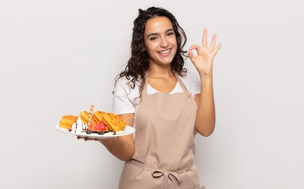 Jeune femme hispanique se sentant heureuse, détendue et satisfaite, montrant son approbation avec un geste correct, souriant