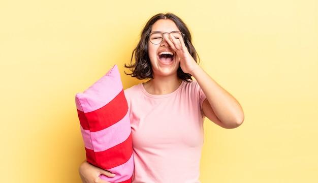 Jeune femme hispanique se sentant heureuse, donnant un grand cri avec les mains à côté de la bouche. concept de réveil matinal