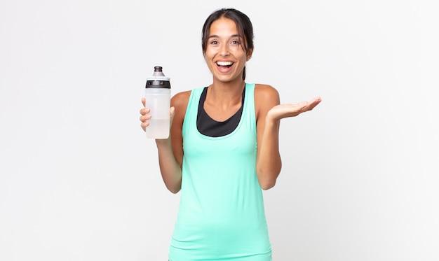 Jeune femme hispanique se sentant heureuse et étonnée de quelque chose d'incroyable et tenant une bouteille d'eau. concept de remise en forme