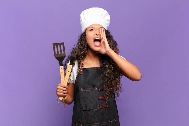 Jeune femme hispanique se sentant heureuse, excitée et positive, donnant un grand cri avec les mains à côté de la bouche, appelant. concept de chef de barbecue