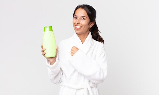 Jeune femme hispanique se sentant heureuse et faisant face à un défi ou célébrant le port d'un peignoir et tenant un shampooing