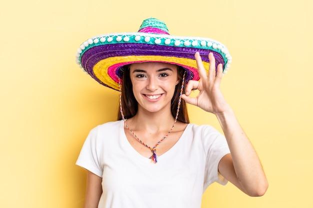 Jeune femme hispanique se sentant heureuse, montrant son approbation avec un geste correct. concept de chapeau mexicain