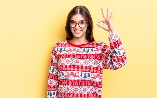 Jeune femme hispanique se sentant heureuse, montrant son approbation avec un geste correct. concept de noël et nouvel an