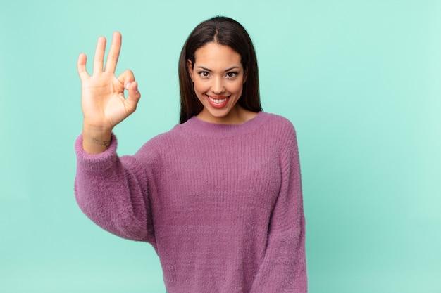 Jeune femme hispanique se sentant heureuse, montrant son approbation avec un geste correct