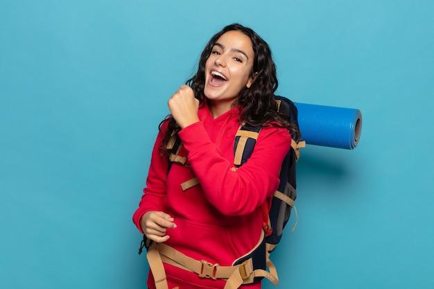 Jeune femme hispanique se sentant heureuse, positive et réussie, motivée face à un défi ou célébrant de bons résultats