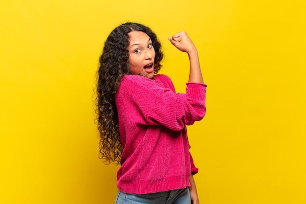 Jeune femme hispanique se sentant heureuse, satisfaite et puissante, ajustement flexible et biceps musclés, ayant l'air fort après la salle de gym