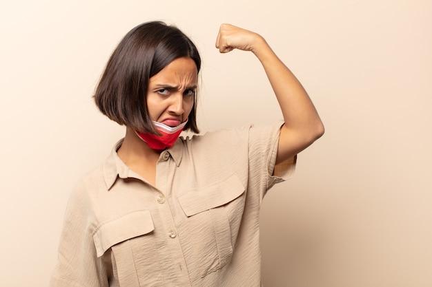 Jeune femme hispanique se sentant heureuse, satisfaite et puissante, flexion et biceps musclés, à la recherche de force après la salle de sport