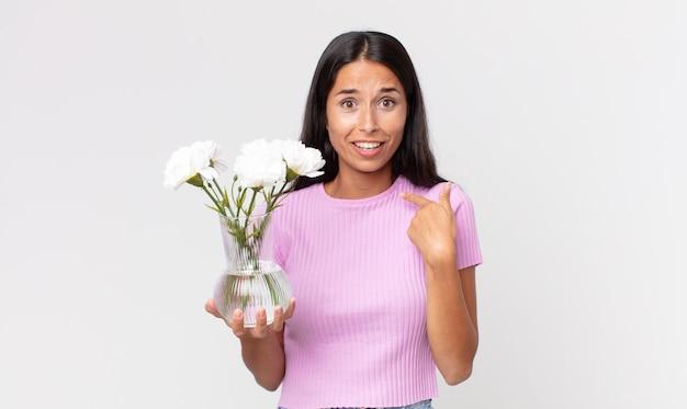 Jeune femme hispanique se sentant heureuse et se montrant elle-même avec une excitation tenant des fleurs décoratives