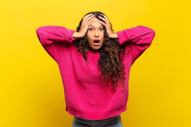 Jeune femme hispanique se sentant horrifiée et choquée, levant les mains à la tête et paniquant devant une erreur