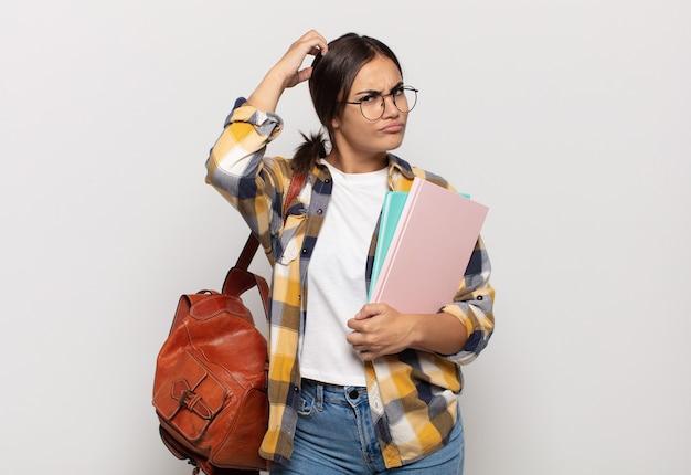 Jeune femme hispanique se sentant perplexe et confus, se gratte la tête et regarde sur le côté