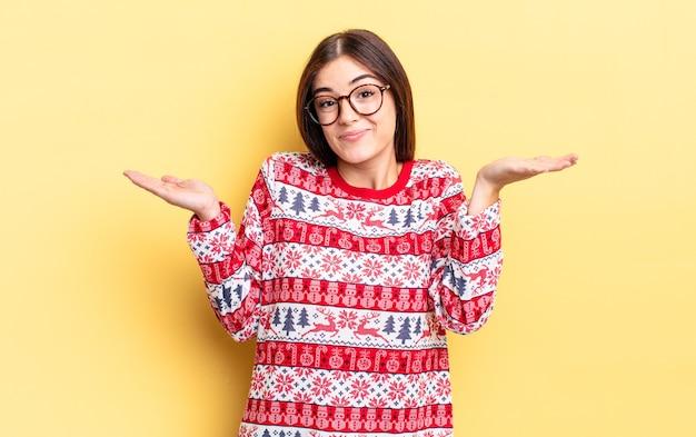 Jeune femme hispanique se sentant perplexe, confuse et doutante. concept de noël et nouvel an