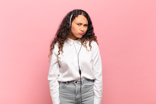 Jeune femme hispanique se sentant perplexe et confuse, avec une expression stupide et abasourdie en regardant quelque chose d'inattendu. concept de télévendeur