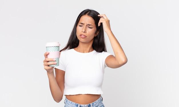Jeune femme hispanique se sentant perplexe et confuse, se grattant la tête et tenant un récipient de café à emporter