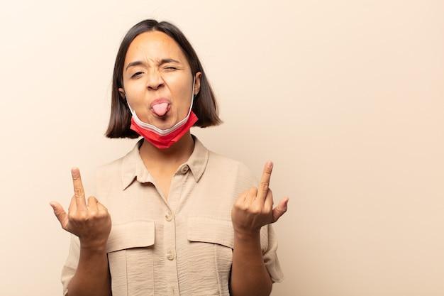 Jeune femme hispanique se sentant provocante, agressive et obscène, retournant le majeur, avec une attitude rebelle