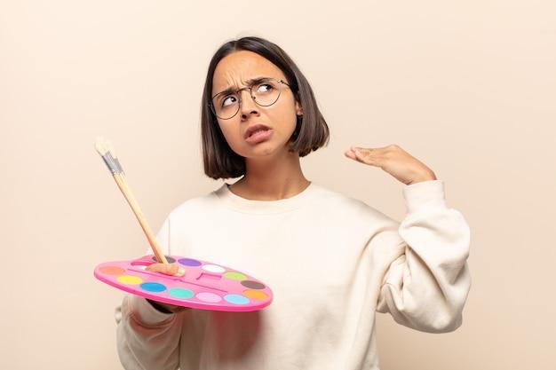 Jeune femme hispanique se sentant stressée, anxieuse, fatiguée et frustrée, tirant le cou de chemise, à la frustration de problème