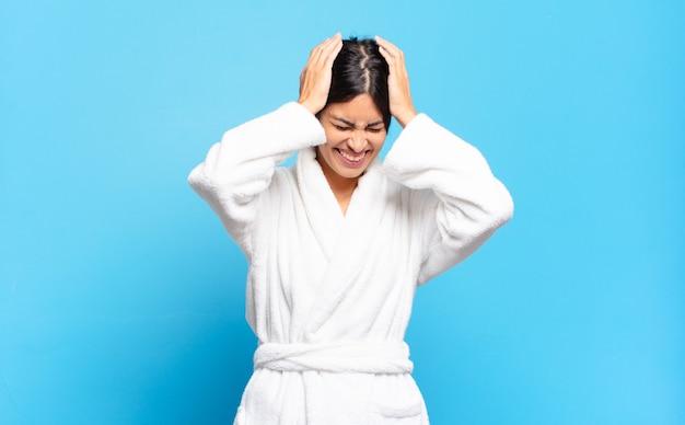 Jeune femme hispanique se sentant stressée et frustrée, levant les mains à la tête, se sentant fatiguée, malheureuse et souffrant de migraine. concept de peignoir
