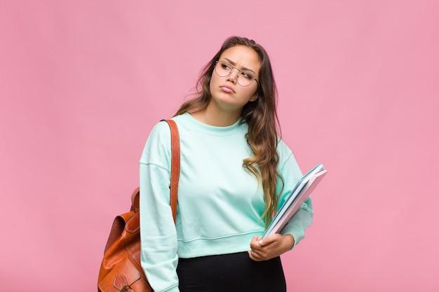 Jeune femme hispanique se sentant triste, bouleversée ou en colère et regardant sur le côté avec une attitude négative, fronçant les sourcils en désaccord