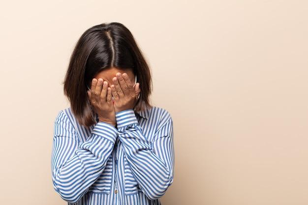 Jeune femme hispanique se sentant triste, frustrée, nerveuse et déprimée, se couvrant le visage des deux mains, pleurant