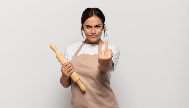 Jeune femme hispanique se sentir en colère, ennuyé, rebelle et agressif, retournant le majeur, ripostant