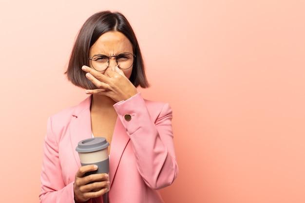 Jeune femme hispanique se sentir dégoûté, se tenant le nez pour éviter de sentir une odeur nauséabonde et désagréable