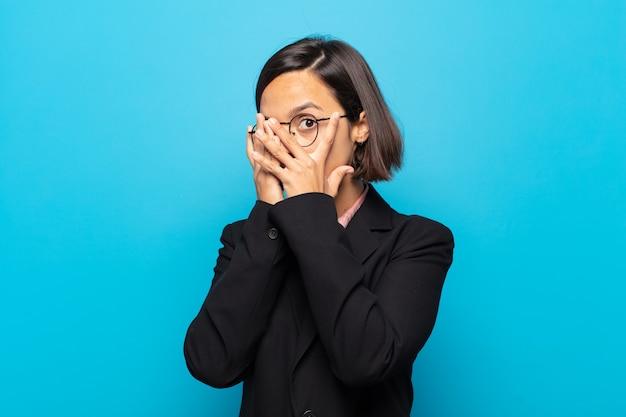 Jeune femme hispanique se sentir effrayée ou gênée, furtivement ou espionnage avec les yeux à moitié couverts de mains