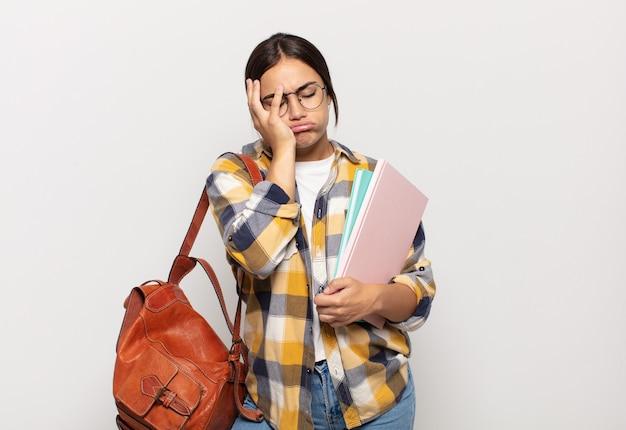 Jeune femme hispanique se sentir ennuyé, frustré et somnolent après une tâche fastidieuse, ennuyeuse et ennuyeuse, tenant le visage avec la main