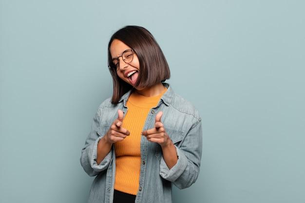 Jeune femme hispanique se sentir heureuse, cool, satisfaite, détendue et réussie, pointant la caméra, vous choisissant