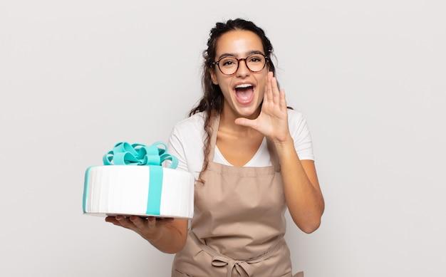 Jeune femme hispanique se sentir heureuse, excitée et positive, donnant un grand cri avec les mains à côté de la bouche, appelant