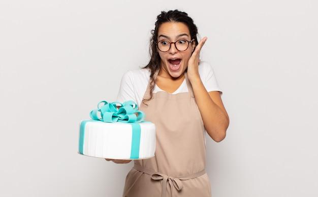 Jeune femme hispanique se sentir heureux, excité et surpris, regardant sur le côté avec les deux mains sur le visage