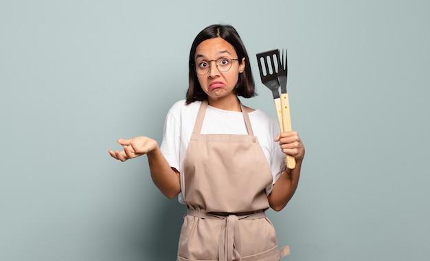 Jeune femme hispanique se sentir perplexe et confus, douter, pondérer ou choisir différentes options avec une drôle d'expression