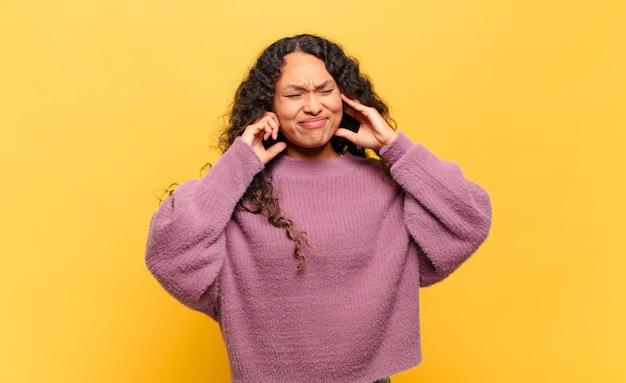 Jeune femme hispanique semblant en colère, stressée et agacée, couvrant les deux oreilles à un bruit assourdissant, un son ou une musique forte