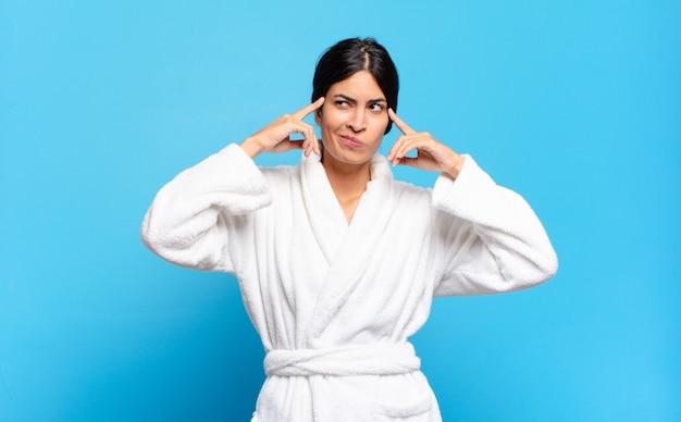 Jeune femme hispanique semblant concentrée et réfléchissant à une idée, imaginant une solution à un défi ou à un problème. concept de peignoir