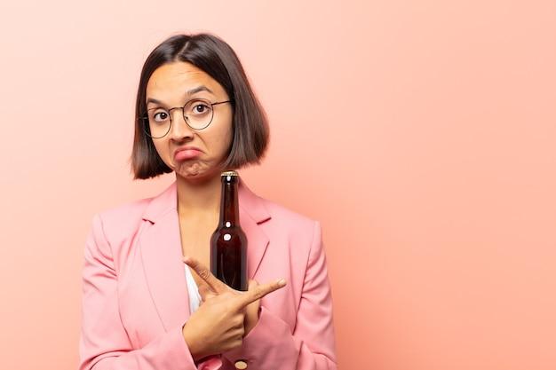 Jeune femme hispanique semblant perplexe et confuse, peu sûre d'elle et pointant dans des directions opposées avec des doutes