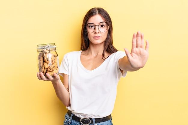 Jeune femme hispanique à la sérieuse montrant la paume ouverte faisant un geste d'arrêt. concept de bouteille de biscuits