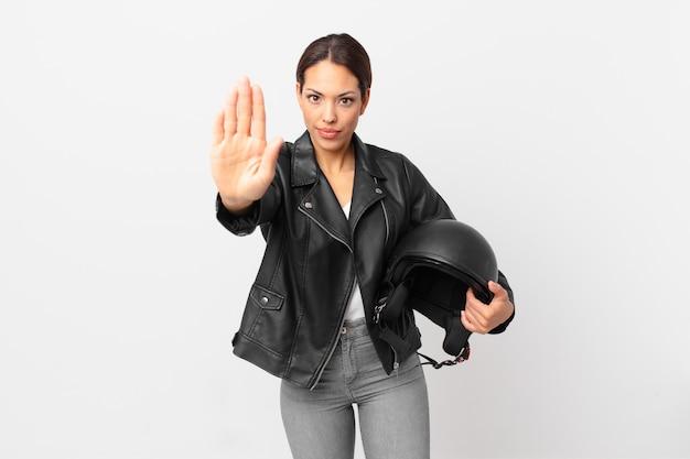 Jeune femme hispanique à la sérieuse montrant la paume ouverte faisant un geste d'arrêt. concept de motard