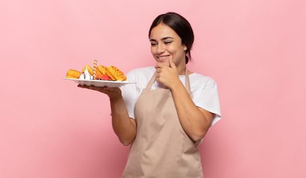 Jeune femme hispanique souriant avec une expression heureuse et confiante avec la main sur le menton, se demandant et regardant sur le côté