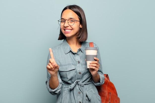 Jeune femme hispanique souriant fièrement et avec confiance en faisant le numéro un pose triomphalement, se sentant comme un leader
