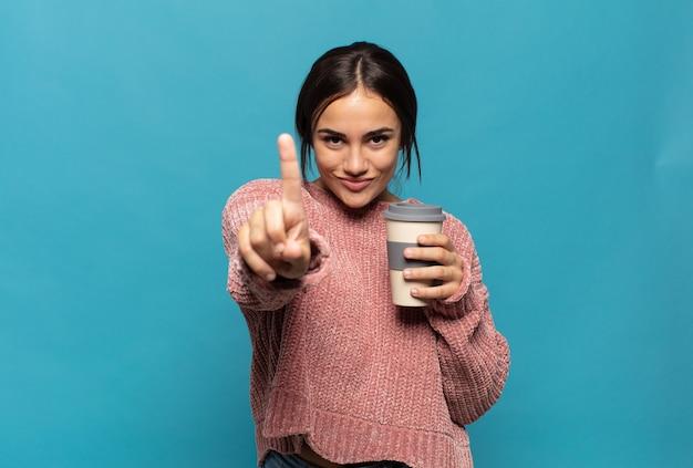 Jeune femme hispanique souriant fièrement et en toute confiance faisant le numéro un pose triomphalement, se sentant comme un leader