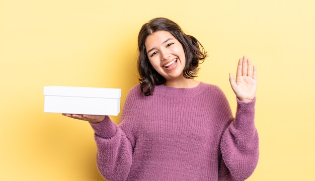 Jeune femme hispanique souriant joyeusement, agitant la main, vous accueillant et vous saluant. concept de boîte vide