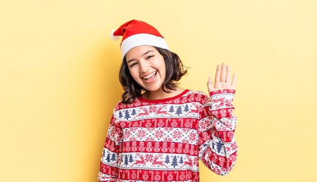 Jeune femme hispanique souriant joyeusement, agitant la main, vous accueillant et vous saluant. notion de noël